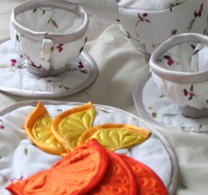 Soft sculptures cups and saucers, made from embroidered fabric, this tea-service comes complete with orange and lemon slices,